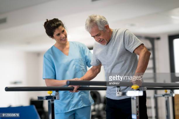 occupational therapist and senior patient working out using parallel bars to walk - bounce back stock photos and pictures