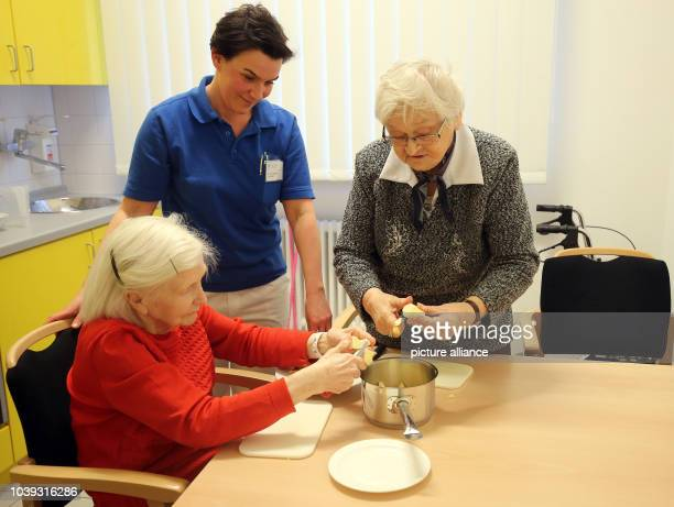 Occupational therapist Anna Nadine Lukowski watches how patients Marlies Lachmund and Edith Sommerfeld peel and cut apples in the practice kitchen at...