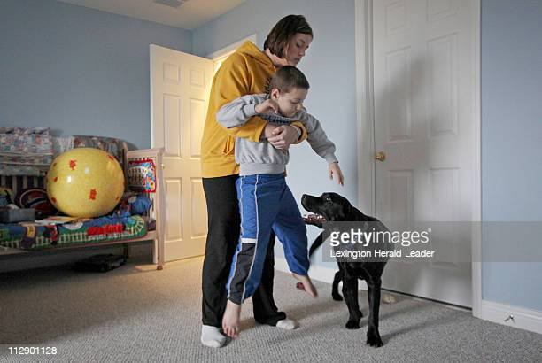 Occupational therapist grad student Jaci Durham helped Michael Farthing an 6yearold with autism during an exercise with a black lab named Mercury who...