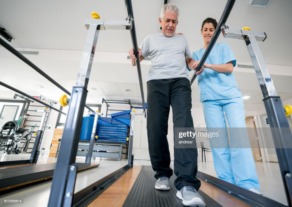 Occupational therapist helping senior patient on his recovery using parallel bars to walk : Stock Photo