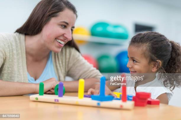 Occupational therapist working with young African American girl at table