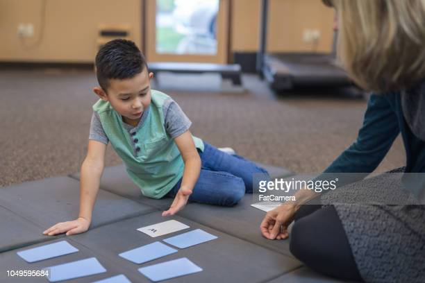 occupational therapist works with a young ethnic boy - coordinazione foto e immagini stock