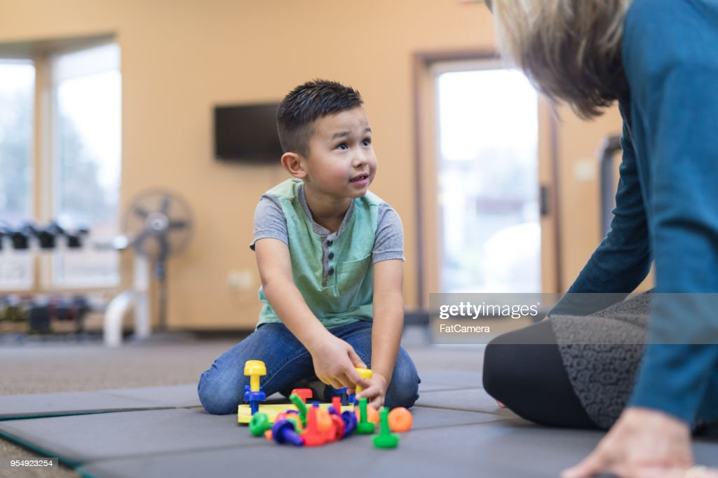 Occupational therapist works with a young ethnic boy : Stock Photo