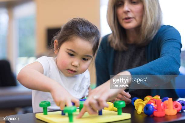 Occupational therapist works with a young ethnic girl