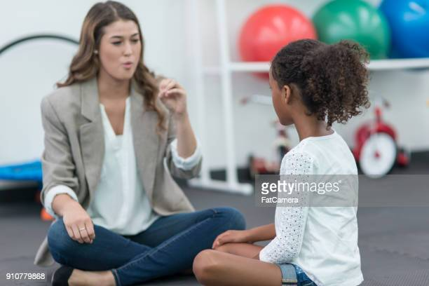 Occupational Therapist Works with a Young Girl in a Modern Clinic