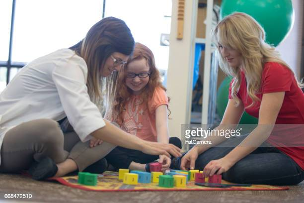 Occupational therapist works with young girl and mother on block building exercise