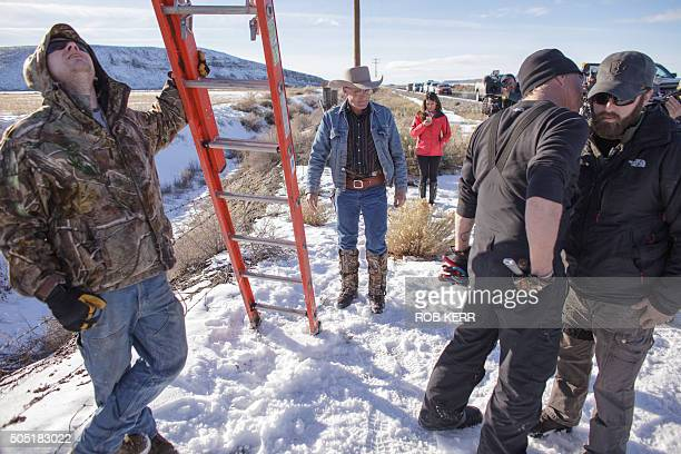 Occupiers confer before disabling a remote camera system mounted on a power pole near the Malheur National Wildlife Refuge Headquarters in Burns...