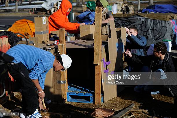 Occupy Denver protester Josh Nichols left from Tacoma Washington helps fellow protesters build 'Castle Occupy' in Civic Center Park Thursday...