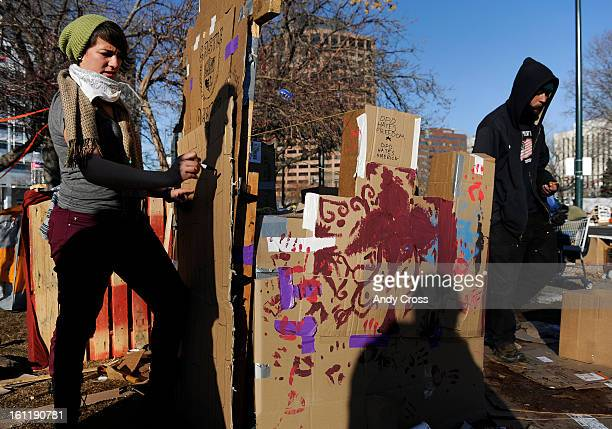 Occupy Denver protester Katherine Abdy left draws 'bricks' on a cardboard drawbridge to an 'Castle Occupy' in Civic Center Park Thursday afternoon...