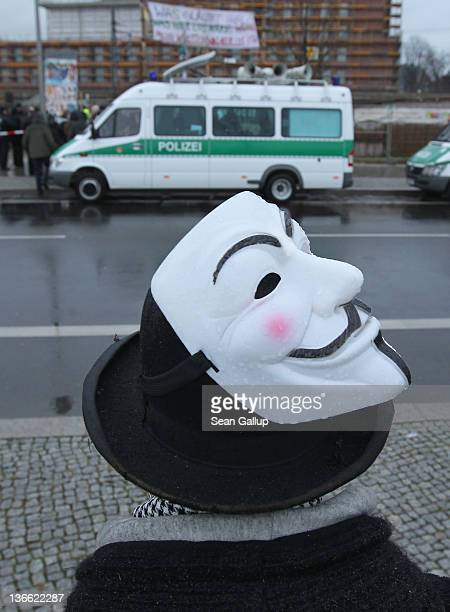 Occupy protester Okan Ozkan wears a Guy Fawkes mask as he stands by while police evict Occupy protesters from a tent camp near Hauptbahnhof train...
