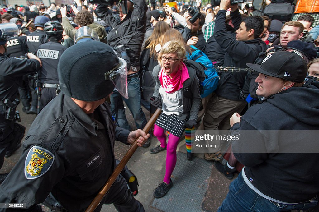Occupy Seattle protesters, an off-shoot of the Occupy Wall Street movement, face off with police officers during a May Day rally and anti-capitalist march in Seattle, Washington, U.S., on Tuesday, May 1, 2012. Occupy Wall Street demonstrators took to the streets in May Day protests from New York to California, picketing banks in Oakland with helicopters overhead and sending a singing 'Guitarmy' to Manhattan's Union Square. Photographer: Stuart Isett/Bloomberg via Getty Images