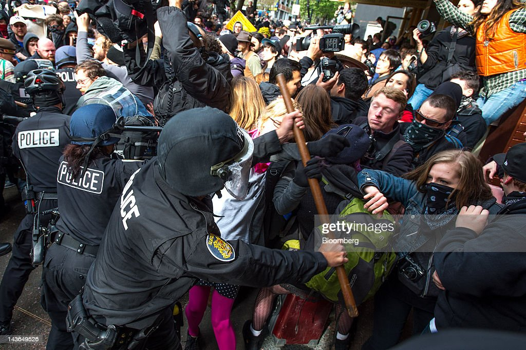Occupy Seattle protesters, an off-shoot of the Occupy Wall Street movement, scuffle with police officers during a May Day rally and anti-capitalist march in Seattle, Washington, U.S., on Tuesday, May 1, 2012. Occupy Wall Street demonstrators took to the streets in May Day protests from New York to California, picketing banks in Oakland with helicopters overhead and sending a singing 'Guitarmy' to Manhattan's Union Square. Photographer: Stuart Isett/Bloomberg via Getty Images