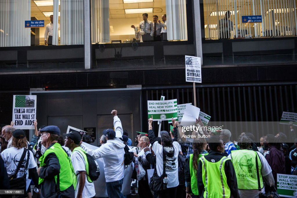 Occupy Wall Street protesters walk past businessmen watching from a window during a march from the United Nations building to Bryant Park on September 17, 2013 in New York City. The march centered around the idea of a so-called Robin Hood Tax, a 0.5 percent levy to be applied to financial service companies, with proceeds to be used for social services. Today marks the two year anniversary since the protestors set up camp in New York's financial district, calling for drastic social and finanical reform.