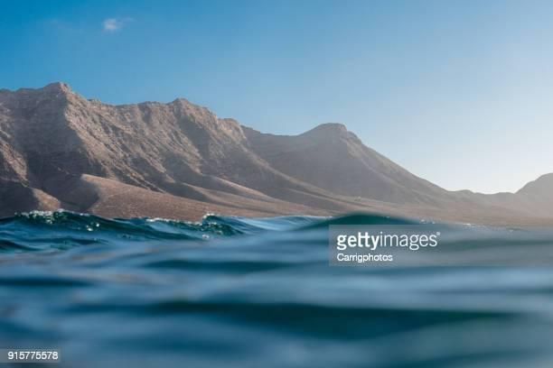 ocean and mountains, cofete beach, fuerteventura, canary islands, spain - islas canarias fotografías e imágenes de stock