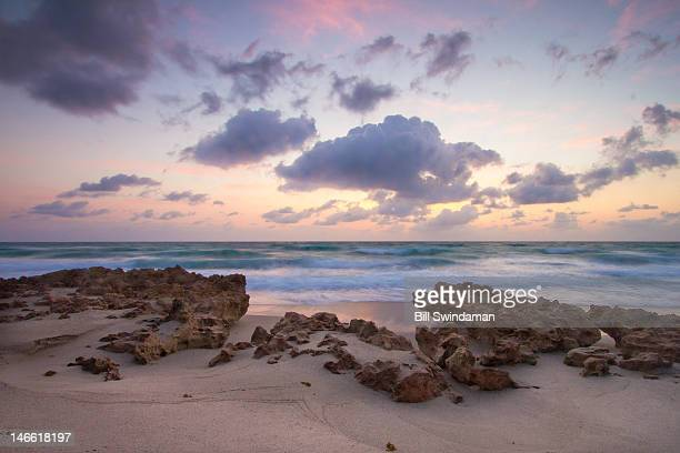 ocean at dawn with clouds and foreground rocks - jupiter island florida stock photos and pictures