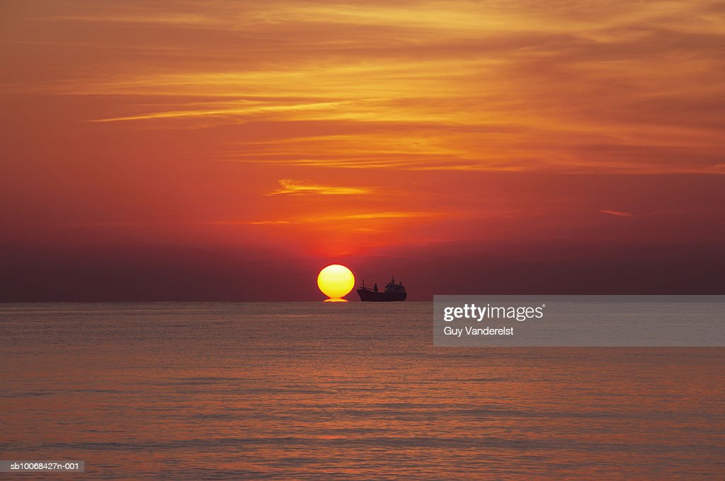 Ocean at sunset with silhouette of ship on horizon : Stock Photo