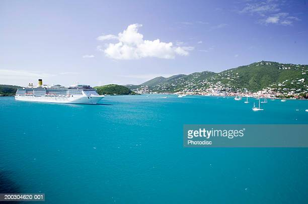 Ocean cruise ship on water by hills and town side, elevated view