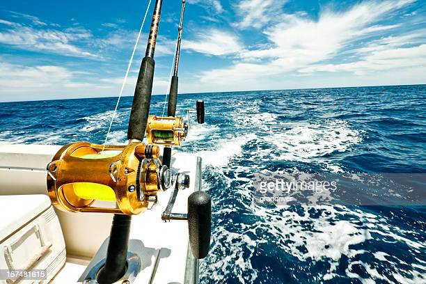 ocean fishing reels on a boat in the ocean - big game fishing stock photos and pictures