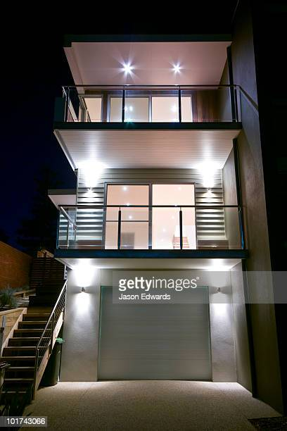 Balconies and a garage in a  modern multi-storey beach house at night.