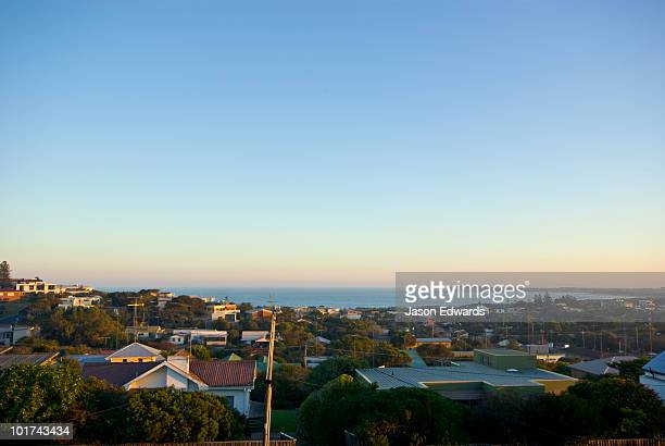 Looking to the sea over the rooftops of a coastal community at sunset.