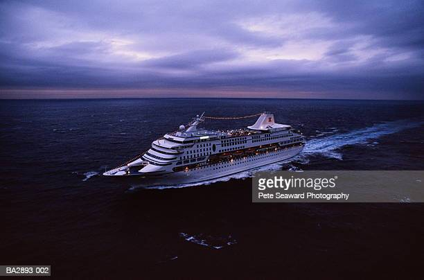 Ocean liner at dusk, decks illuminated, aerial view
