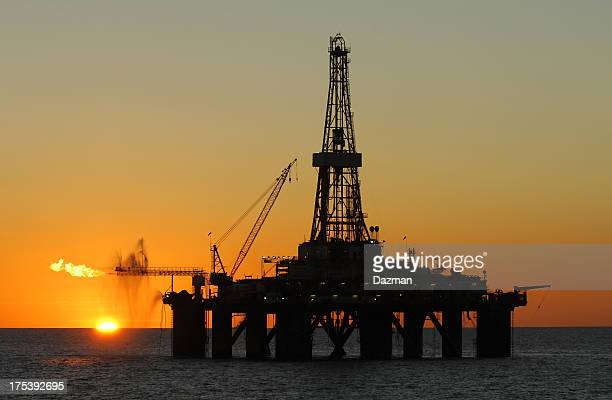 Ocean oil rig silhouette at sunset.