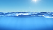 Ocean or sea in half water half sky. Rays of sunlight shining from above penetrate deep clear blue water. Realistic dark blue ocean surface. View - half of the sky, half water. 3D rendering