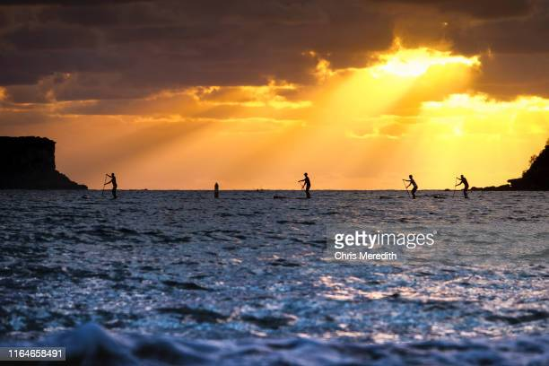 ocean paddleboarders silhouetted against dramatic sun beams - sydney chase stock pictures, royalty-free photos & images
