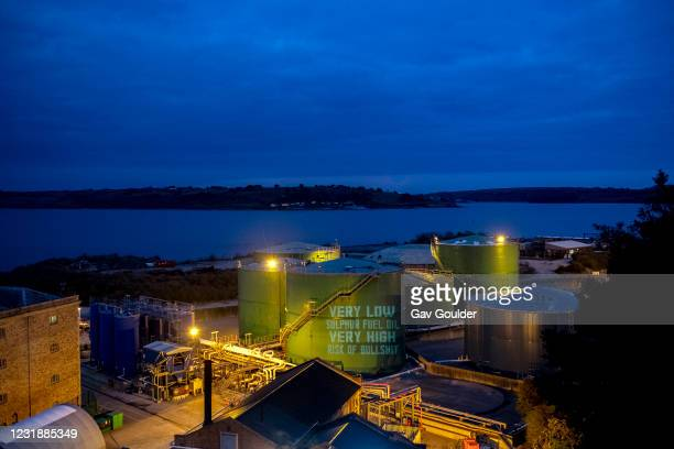 Ocean Rebellion protest in Falmouth Harbour in Cornwall at sun down by projecting slogans and messages onto fuel silos calling for the shipping...