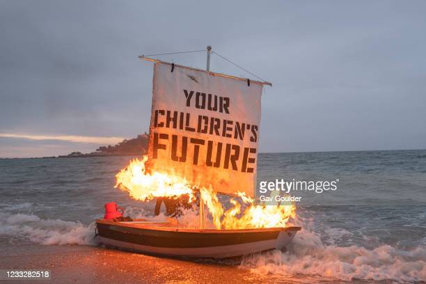 Ocean Rebellion staged a theatrical action with a Boris Johnson head and an Oilhead sitting in deckchairs on Marazion beach while a boat burns in the...