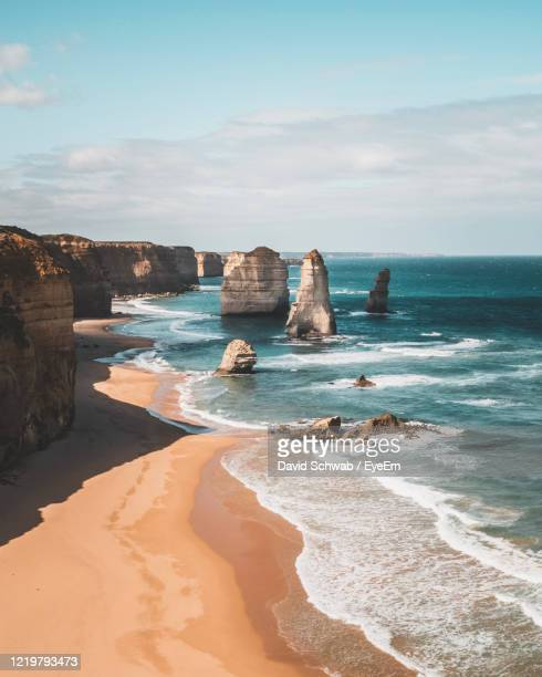 ocean rock formation and cliffs on beach against sky in great ocean road australia - melbourne australia stock pictures, royalty-free photos & images