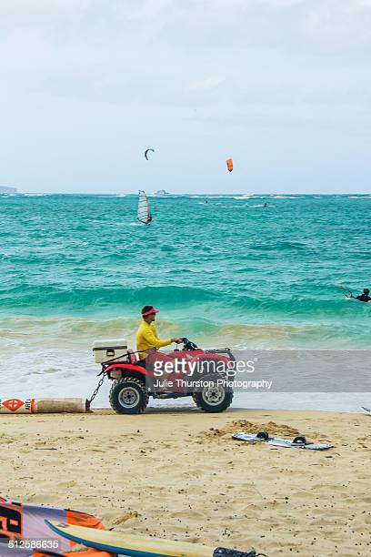 Ocean Safety Lifeguard Riding a 4 Wheel ATV Along the Shoreline While Water Sport Lovers Enjoy Recreational Kitesurfing and Windsurfing in the...