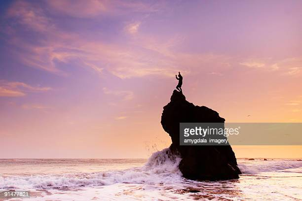 ocean sky sunset and man arms raised rock formation - malibu beach stock pictures, royalty-free photos & images