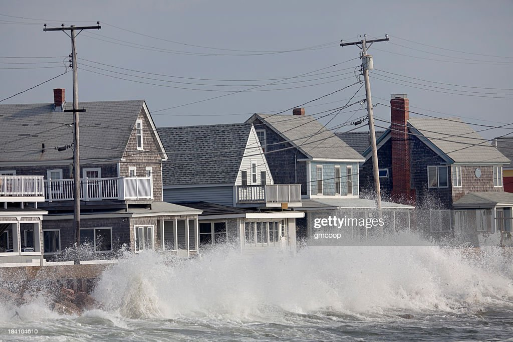 Ocean Storm Waves Crashing into Seawall in front of Houses : Stock Photo