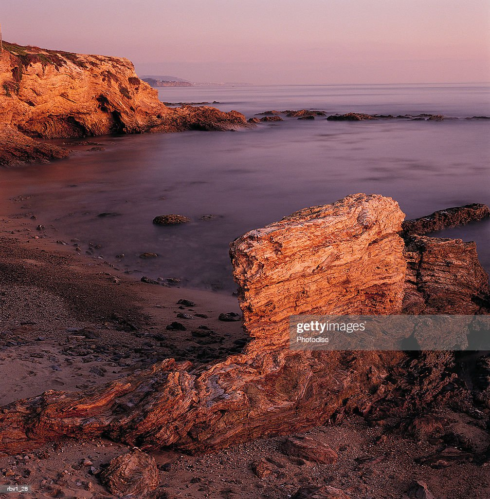 ocean water rushes against jagged rocks onto a sloping beach covered with sand as the sun sets : Foto de stock