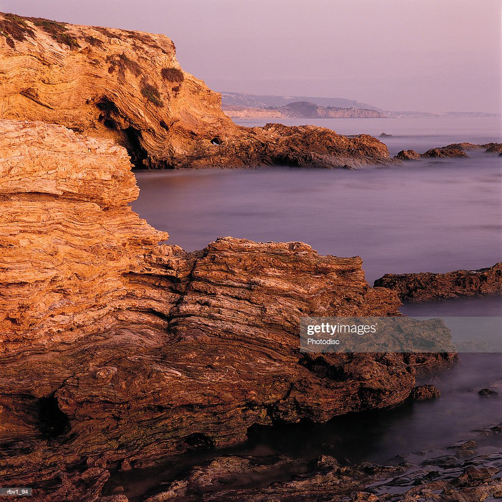 ocean water rushes against rocks on a coast line as the sun sets : Foto de stock