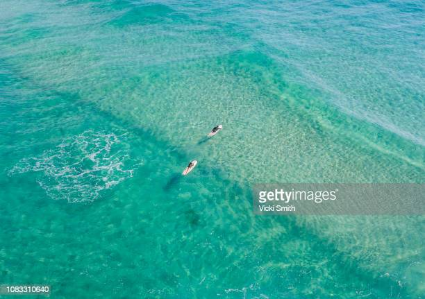ocean waters with surfers seen from above - gold coast queensland stock pictures, royalty-free photos & images
