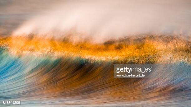 Ocean wave breaking at sunset