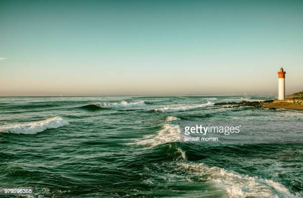 ocean waves and lighthouse, durban, kwazulu natal, south african - durban beach stock photos and pictures