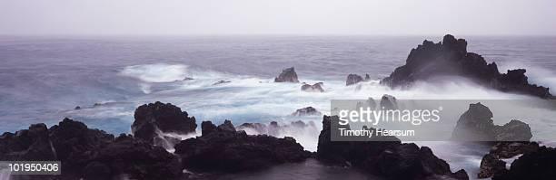 ocean waves crashing against lava rock - timothy hearsum stock-fotos und bilder