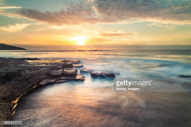 ocean waves flowing over rocks at sunrise with orange and gold clouds - seascape stock pictures, royalty-free photos & images
