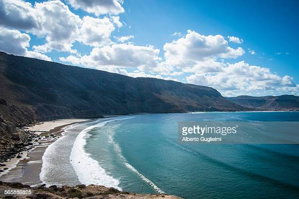 Ocean waves on beach under mountains