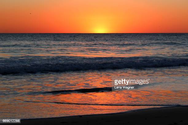 Ocean waves reflecting orange sunset