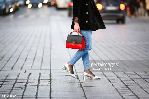 Oceane Grilhe wears Stradivarius silver shoes, Calzedonia fishnet tights, Stradivarius blue denim jeans pants, a Morgan black jacket, a black and red...