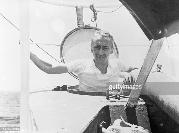 Oceanographer Jacques Cousteau emerges halfway out of submarine hatch