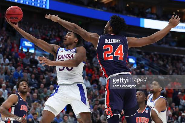 Ochai Agbaji of the Kansas Jayhawks goes up for a shot against Anfernee McLemore of the Auburn Tigers during their game in the Second Round of the...