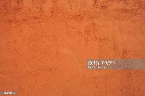 ochre colored wall texture - marrón fotografías e imágenes de stock