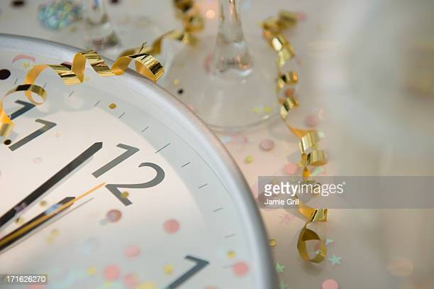12 o'clock on clock decorated with confetti and streamer - countdown clock stock-fotos und bilder