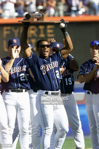 San Diego Padres outfielder Rickey Henderson holds up a plaque given to him by teammates immediately following his 3000th hit, versus the Colorado...