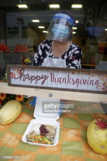 Oct. 10, 2020 -- A volunteer wearing a face mask and a shield distributes a meal at a booth during the Thanksgiving dinner event in Vancouver,...
